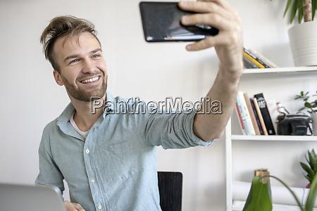 laechelnder mann der ein selfie am