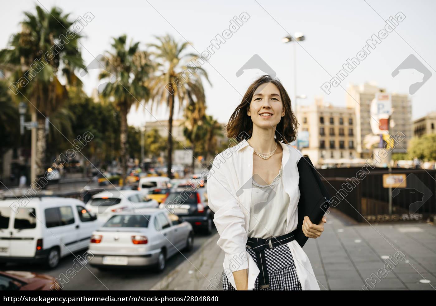 pretty, businesswoman, carrying, folder, , walking, in - 28048840