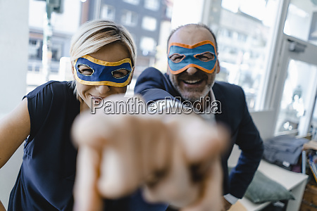 geschaeftsmann und frau die superheldenmasken tragen