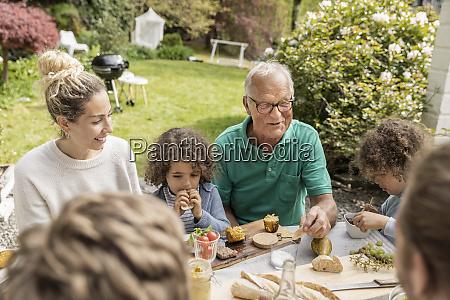 erweiterte familie beim mittagessen im garten