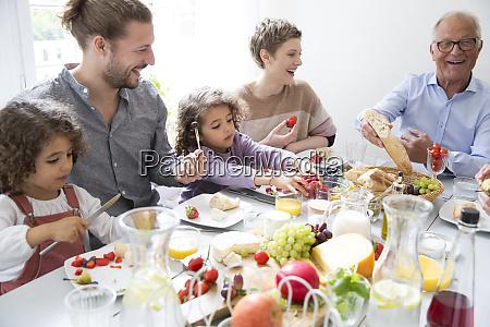 glueckliche grossfamilie beim mittagessen zu hause