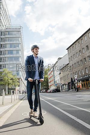 junger geschaeftsmann faehrt e scooter auf