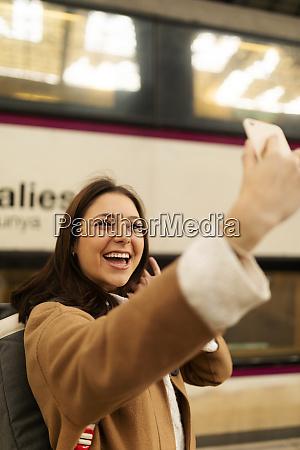 glueckliche junge frau macht ein selfie