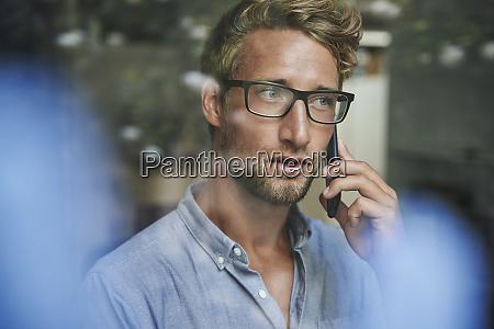 laessiger junger geschaeftsmann am telefon hinter