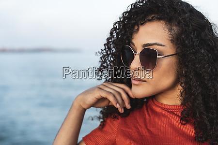 beautiful woman wearing sunglasses standing at