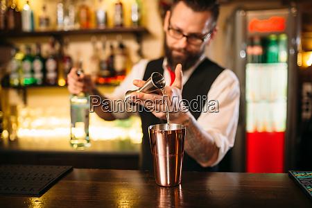 bartender giesst alkoholgetraenk in metallglas