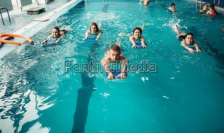 maennlicher trainer schwimmt mit weiblicher aqua