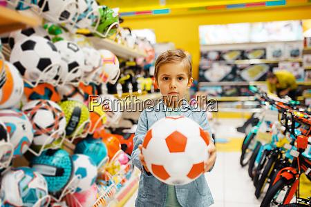 kleiner junge mit ball in kindergeschaeft