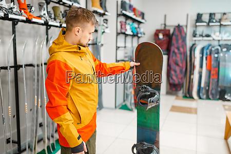 mann waehlt snowboard einkaufen im sportgeschaeft