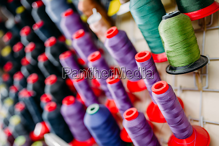 colorful threads on spools closeup sewing