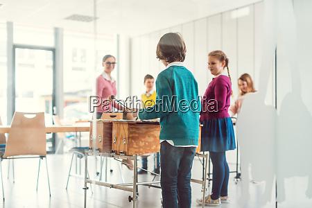 musiklehrer mit schuelern im unterricht am
