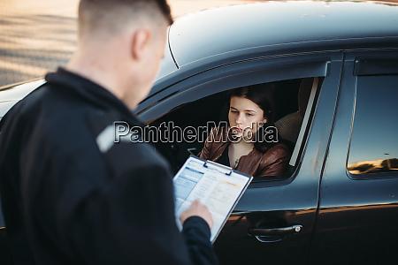 polizist in uniform schreibt geldstrafe auf