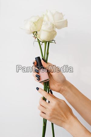 frau haelt nagellack und blumen schoenheitssalon