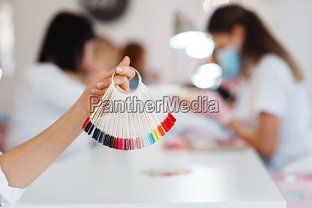 frau haelt nagellack farbpalette