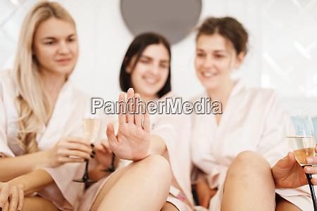 gruppe von freundinnen mit champagner schoenheitssalon
