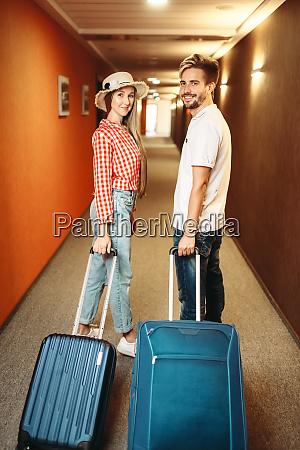 laechelndes paar mit koffer im hotelflur