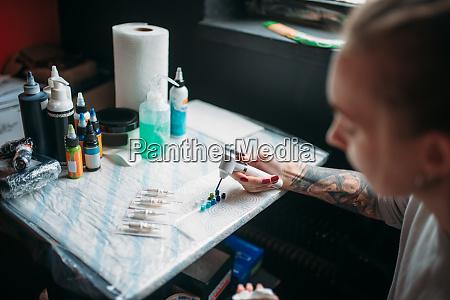 weibliche tattoo kuenstlerin bereitet farbe tinte