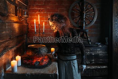 gruselige hexe liest zauber ueber den