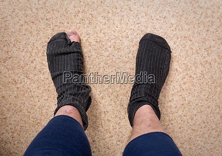 maennliche fuesse mit socke im loch