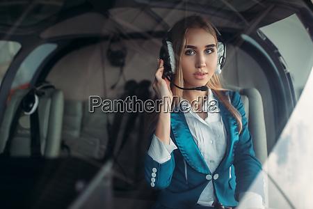 pilotin in kopfhoerern in hubschrauberkabine