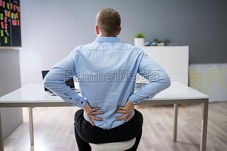 geschaeftsmann leidet unter rueckenschmerzen