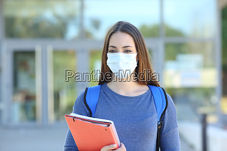 student wearing a mask walking in