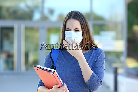 ill student with a mask coughing