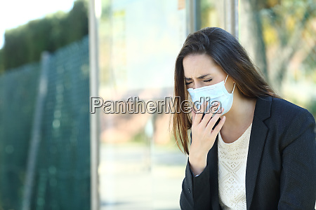 infected woman wearing a mask coughing