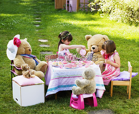 zwei junge maedchen spielen teddybaeren picknick