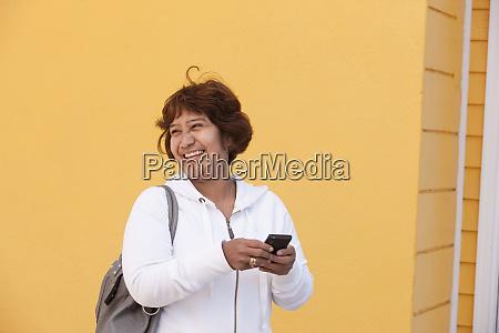 a senior woman stands against a