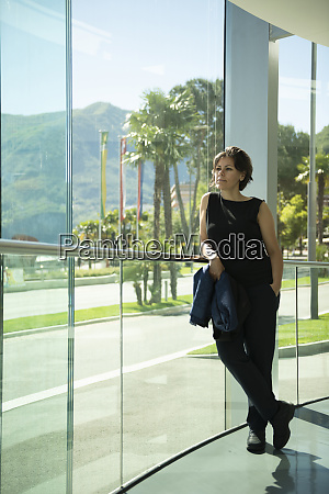 a woman stands at a windowed