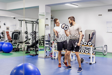 mann coaching freund in fitness studio