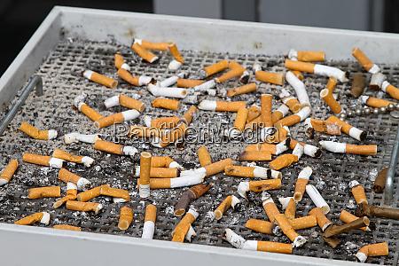 grosser aschenbecher mit vielen geraeucherten zigaretten