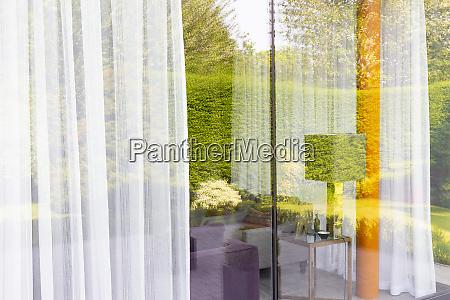 gartenreflexion ueber moderne raumhohe wohnzimmerfenster