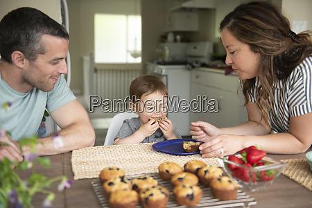 junge familie isst frische muffins in