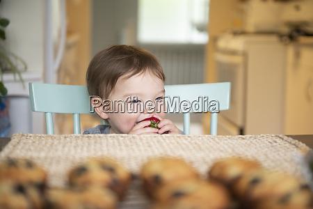 suesses kleinkind maedchen essen erdbeere