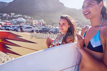junge frauen mit surfbrettern am sonnigen