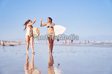 glueckliche junge surferin freunde hoch fiving