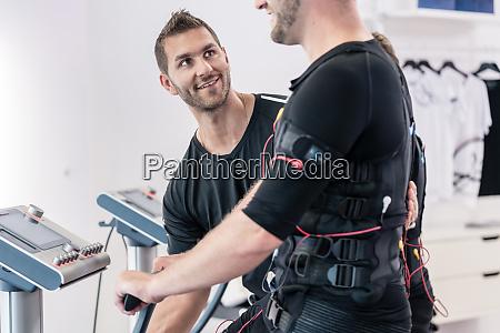 trainer hilft mann in ems fitnessstudio