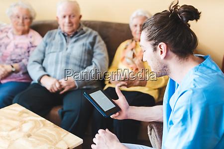 nurse reading to senior men and