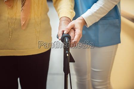krankenschwester im pflegeheim hilft einer seniorin