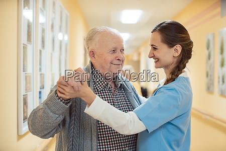 krankenschwester und senior tanzen im saal