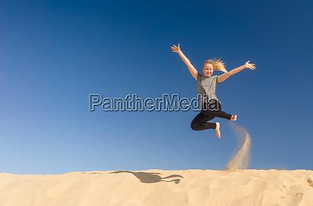 ein junges maedchen springt im sommer