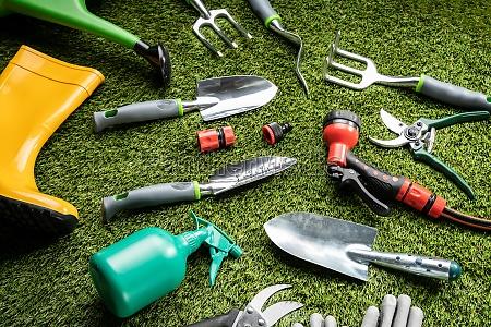 verschiedene gartenwerkzeuge auf gras legen