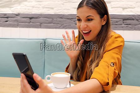 joyful girl video calling friend on