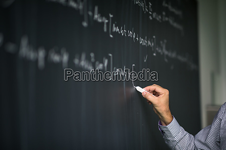 mathelehrer an der tafel waehrend des