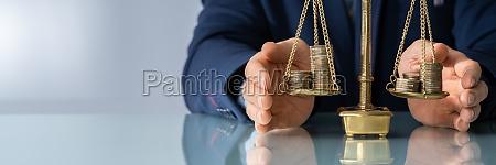 anwaltshand schutzt gerechtigkeitsskala mit muenzen