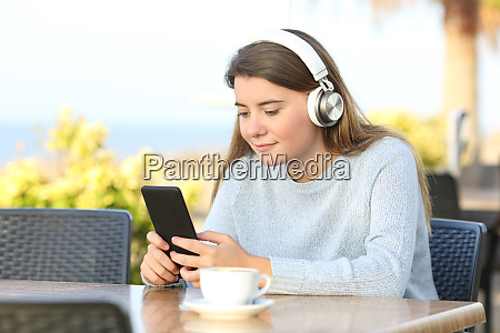 maedchen hoert musik in einem cafe