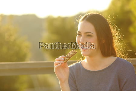 happy woman eating a cereal bar