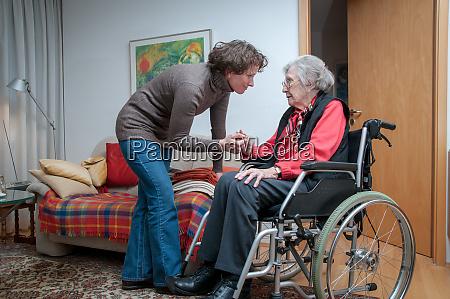 betreuerin hilft seniorin im rollstuhl sitzend